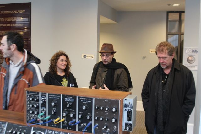 """Michelle Moog-Koussa, BMF Executive Director, shows Bob Boilen of NPR's """"All Songs Considered"""" the intriguing inside view of the modular circuitry as Moog Guitar inventor Paul Vo looks on."""